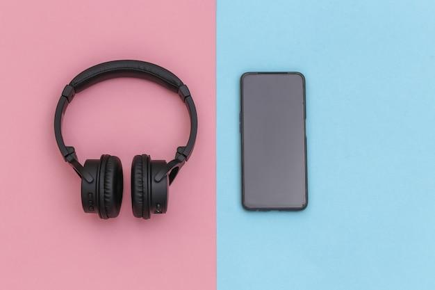 ピンクブルーのパステルカラーの背景にワイヤレスステレオヘッドフォンとスマートフォン。上面図