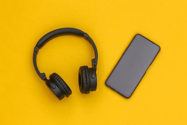 黄色の背景にワイヤレスステレオヘッドフォンとスマートフォン。上面図