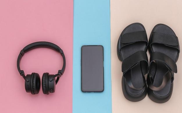 ワイヤレスステレオヘッドフォンとスマートフォン、ピンクブルーのパステルカラーの背景にサンダル。上面図