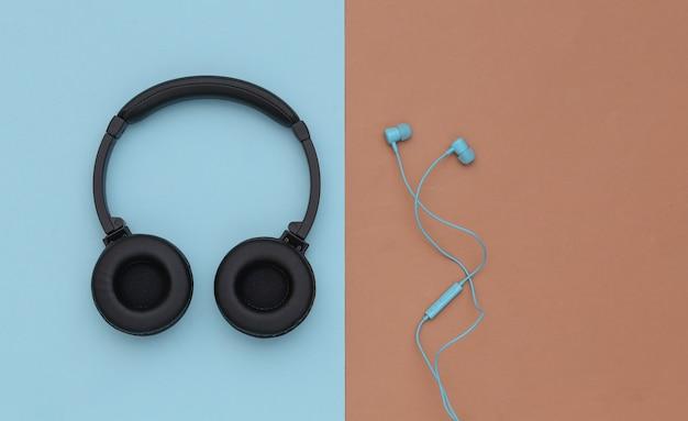 파란색 갈색 배경에 무선 스테레오 헤드폰과 유선 이어폰. 평면도. 플랫 레이