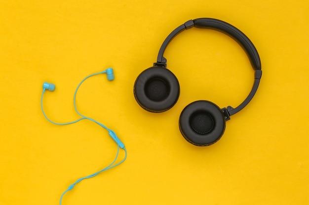 노란색 배경에 무선 스테레오 헤드폰과 유선 이어폰. 평면도. 플랫 레이
