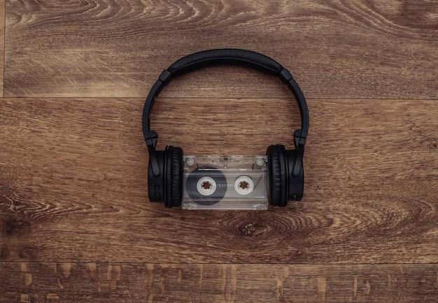 木製の背景にオーディオカセット付きのワイヤレスステレオヘッドフォン。上面図