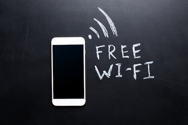 Wireless symbol drawn on a blackboard near smartphone