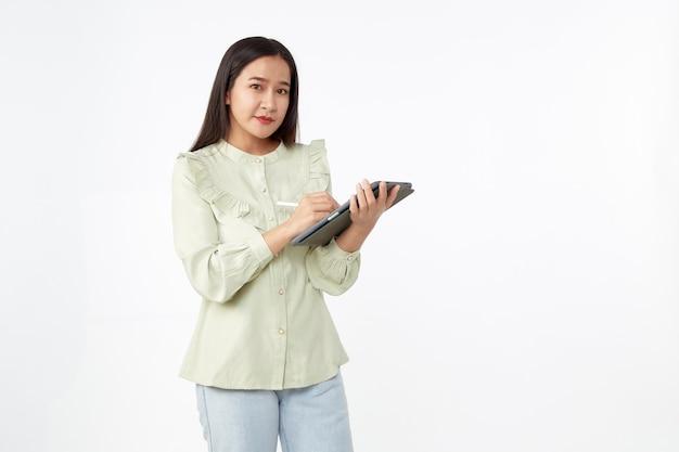 Беспроводная технология. красивая молодая азиатская женщина держа цифровую таблетку и смотря камеру с улыбкой стоя изолированной на белой предпосылке.