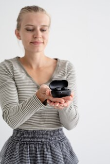 ワイヤレステクノロジー。ワイヤレスイヤフォンを保持している若い女性
