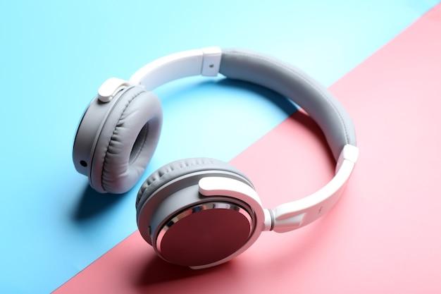 ピンクブルーのスペースにワイヤレスの白とグレーのヘッドフォン