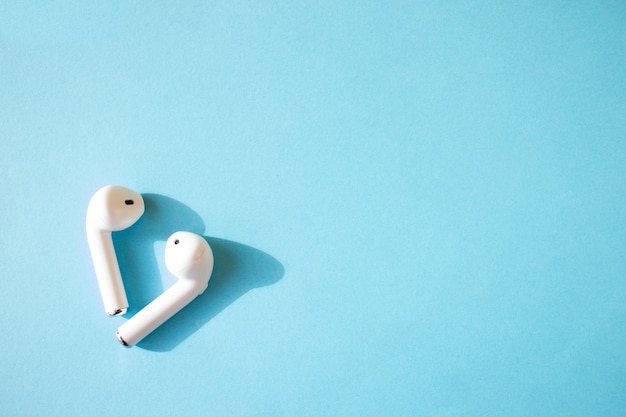 파란 벽에 무선 화이트 헤드폰