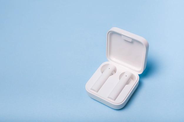 無地の背景にワイヤレスの白いヘッドホン白いヘッドホン無地の背景現代の電子機器未来の技術ワイヤレス音楽再生bluetoothヘッドホン