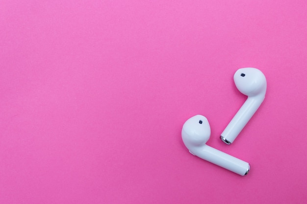 Wireless white headphones on pink