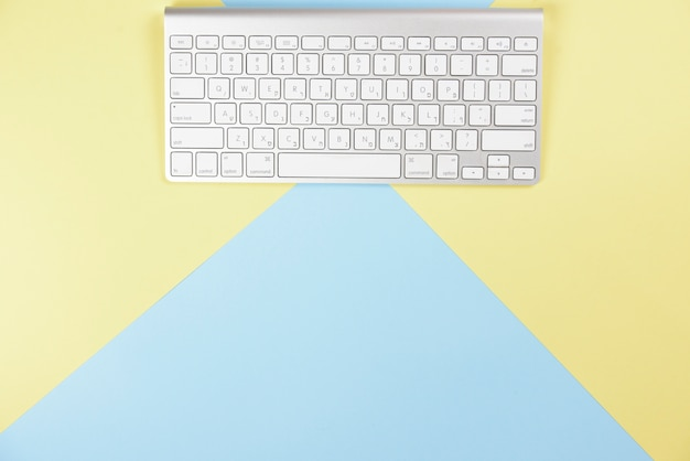 Wireless white keyboard on yellow and blue background