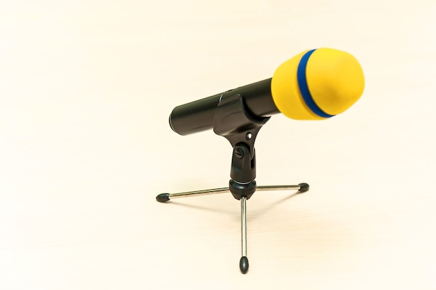 Wireless yellow microphone with stand on white table for speaking speakers at conference