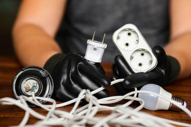 남성 전기 기사의 손에 전선, 소켓 및 플러그. 전구. 전선, 전기 네트워크를 수리합니다. 고품질 사진