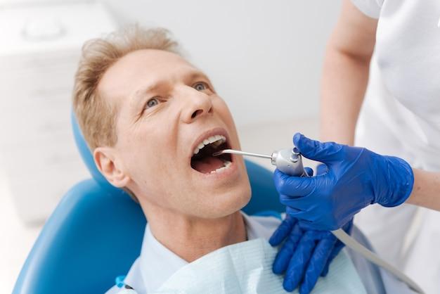 Мудрый, привлекательный, достойный восхищения джентльмен навещает своего стоматолога и лечится, лежа в специальном кресле
