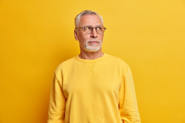 Wise intelligent bearded man concentrated away with thoughtful expression gazes determined on right has thick grey beard wears transparent glasses and casual jumper isolated over yellow wall