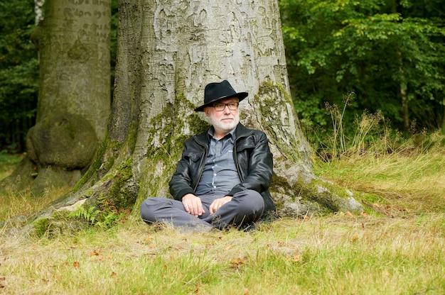 숲에서 나무 아래 앉아 현명한 노인