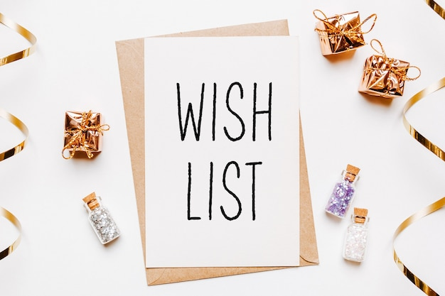 Wish list note with envelope, gifts and gold glitter stars on white background. merry christmas and new year concept