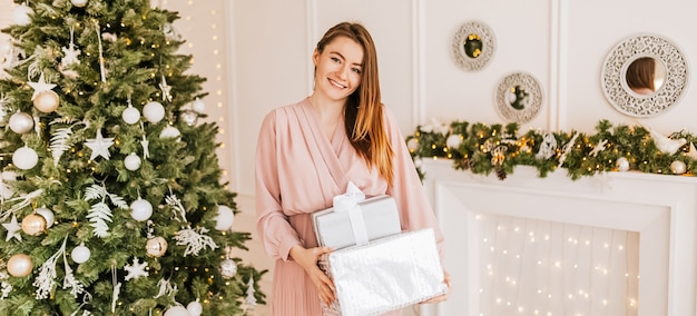 Wish you a merry christmas. girl with a gift presents. happy feeling to new year.