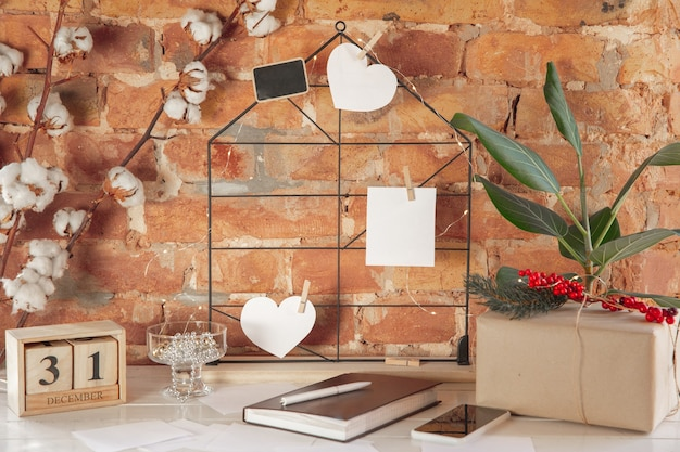 Желания, мечты о планах целей на доске настроения напротив кирпичной стены. женские руки на фоне деревянного календаря, подарочной коробки на новый год, зимние праздники и рождество. готовим мудборд.