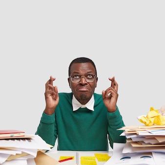 Мужчина-афроамериканец, желающий желать удачи, скрестил пальцы на удаче, одетый в элегантный зеленый свитер