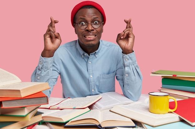 희망찬 검은 피부의 남자는 행운을 위해 손가락을 교차하고, 빨간 모자와 안경을 쓰고, 시험 세션 전에 행운을 믿습니다.