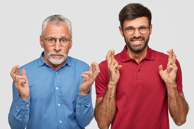 Wishful father and young adult son posing against the white wall