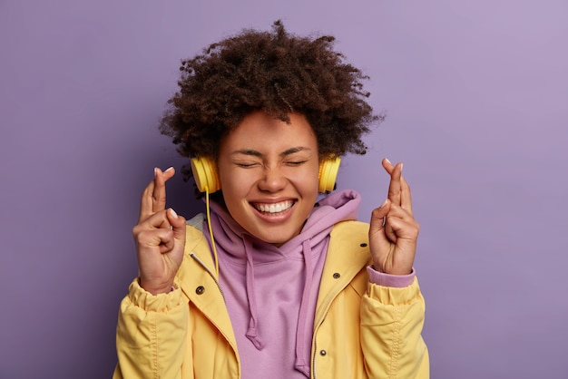 Wishful happy woman with natural curly hair anticipates relish and good news, crosses fingers and smiles broadly, awaits for dream come true, wears stereo headphones, listens pleasant music.