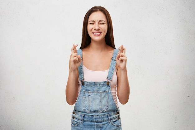 Желание и сильное желание концепции. портрет красивой отчаянной молодой европейской женщины в джинсовом комбинезоне, скрестив пальцы и плотно закрывая глаза, загадывая желание, ее выражение лица полно надежды