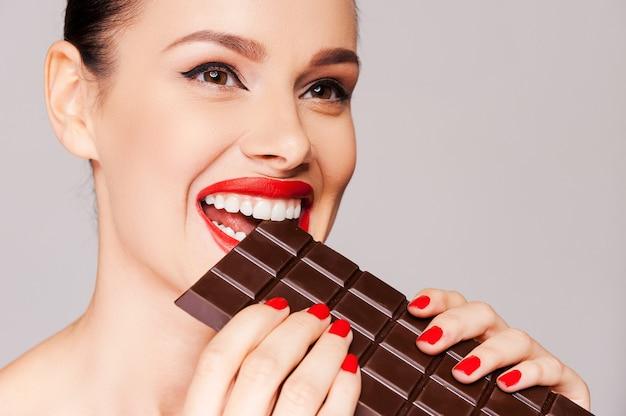 チョコレートが実りました。灰色の背景に立っている間彼女の赤い唇に指を保持している美しい女性のクローズアップ