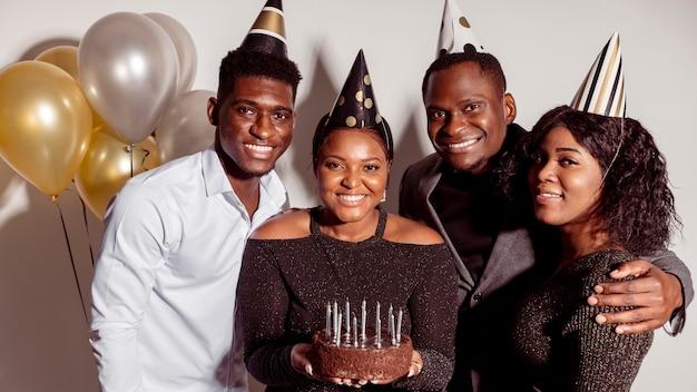 Augurando buon compleanno e donna che tiene la torta