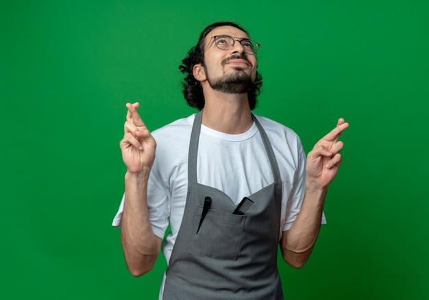 Пожелание молодого кавказского парикмахера в очках и волнистой повязке для волос в униформе смотрит вверх и скрещивает пальцы, изолированные на зеленом фоне с копией пространства