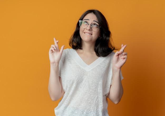 Желая молодой красивой кавказской девушки в очках, глядя вверх и делая жест скрещенными пальцами, изолированный на оранжевом фоне с копией пространства