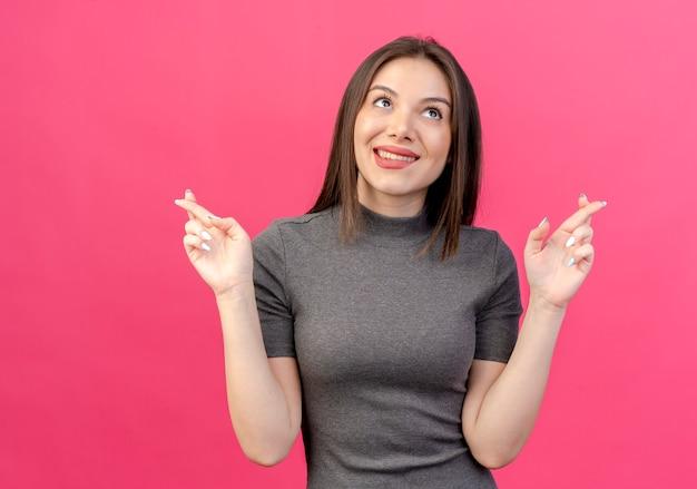 唇を噛んで見上げて、コピースペースでピンクの背景に分離された交差した指のジェスチャーをしている若いきれいな女性を願っています