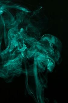 Тонкий зеленый дым распространяется на черном фоне
