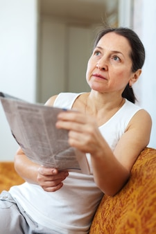 Wistful  woman with newspaper