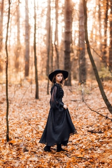 Witch in the autumn forest. a girl in a black long dress walks in the forest.