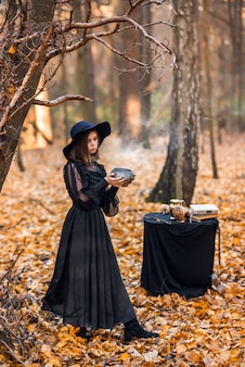 A witch in the autumn forest. a woman in a black long dress cooking a potion is preparing for halloween