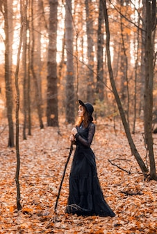 Witch in the autumn forest. a woman in a black long dress with a cane