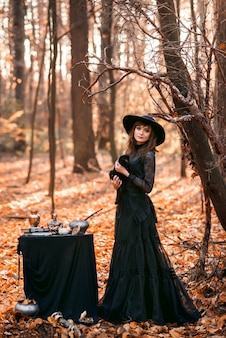 Witch in the autumn forest. a woman with a black cat is preparing for halloween.
