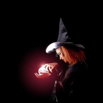 Witch in black are spelling dark magic with marble.