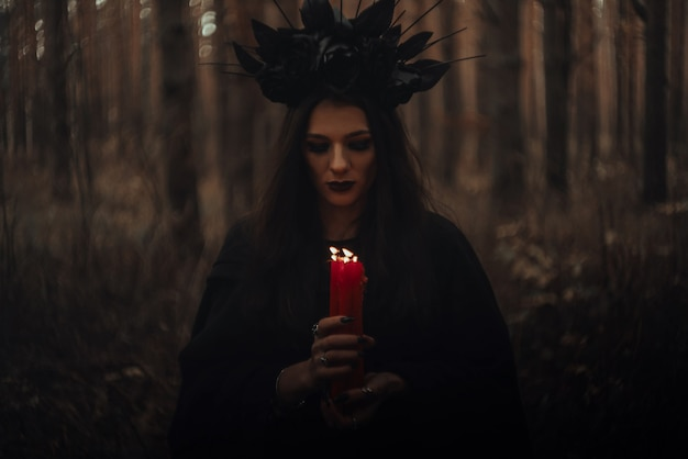 Witch in a black costume holds candles in a dark gloomy forest