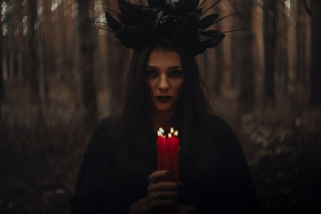 Witch in a black costume holds candles in a dark gloomy forest Premium Photo