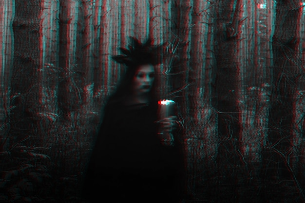 Witch in a black costume performs dark spells with candles in the forest. blurry photo with blurring due to long exposure time. black and white with 3d glitch virtual reality effect