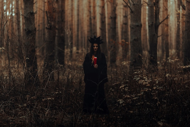 Witch in a black costume performs dark spells with candles in the forest