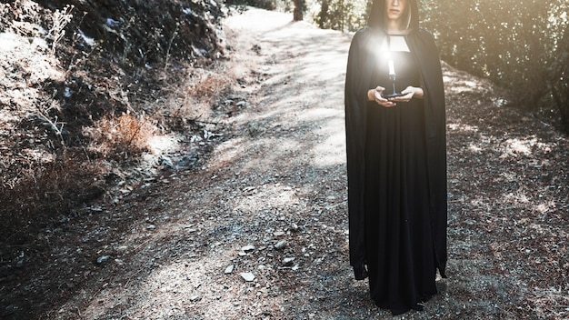 Witch in cape holding candlestick on forest path