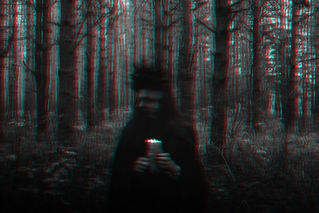 Witch in costume performs dark spells with candles in the forest. blurry photo with blurring due to long exposure time. black and white with 3d glitch virtual reality effect