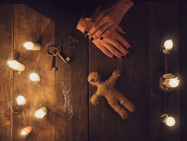 A witch in the dark holds a voodoo rag doll surrounded by candles, flat lay.