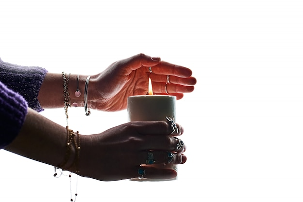 Witch fortune teller woman holding burning candle with flame in hands for witchcraft and fortune telling on a white wall
