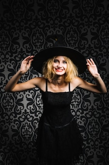 Witch girl holding hat and smiling