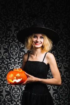 Witch girl smiling and holding pumpkin
