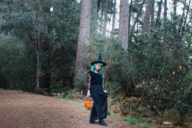 Девушка-ведьма, идущая в лесу